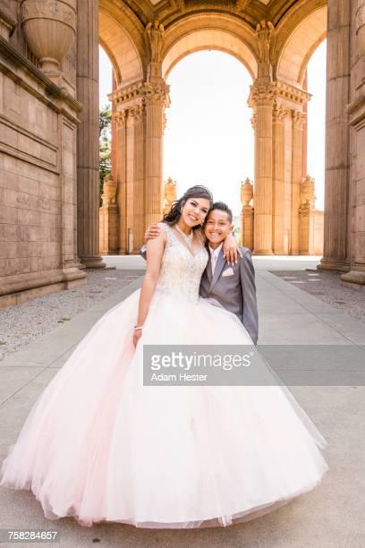 Hispanic girl wearing gown hugging boy