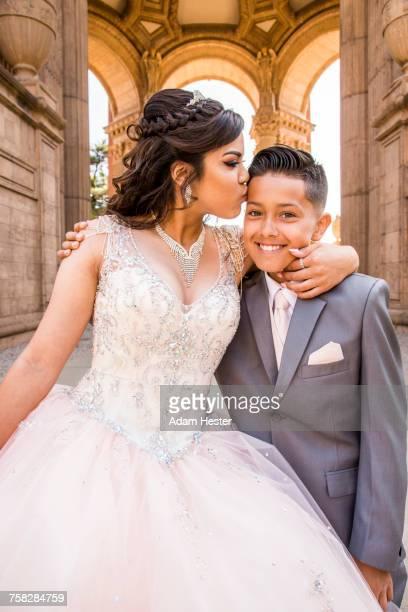 Hispanic girl wearing gown kissing boy on forehead