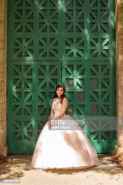 Hispanic girl wearing gown standing near green wall