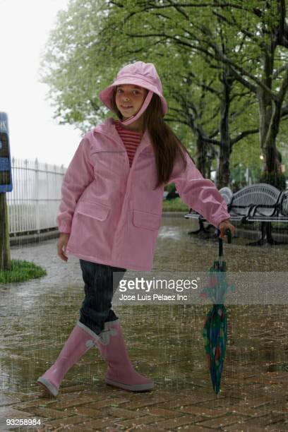 Hispanic girl wearing rain gear in rainy park