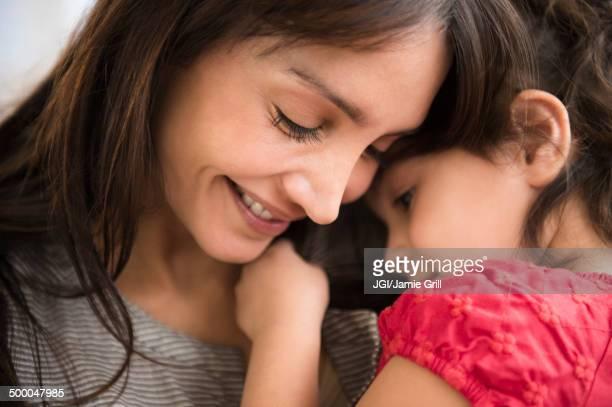 Hispanic girl whispering in mother's ear