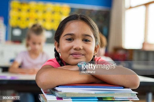 Hispanic girl with chin on books : Foto de stock