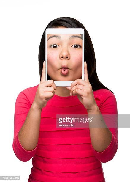 Hispanique fille avec tablette numérique en drôle des autophotos