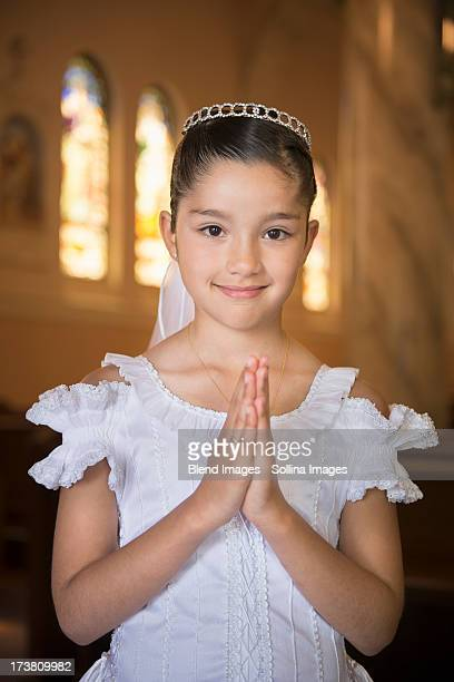 Hispanic girl with hands clasped in church