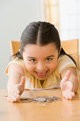 Hispanic girl with pile of coins