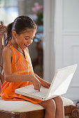 Hispanic girl working on a laptop and smiling