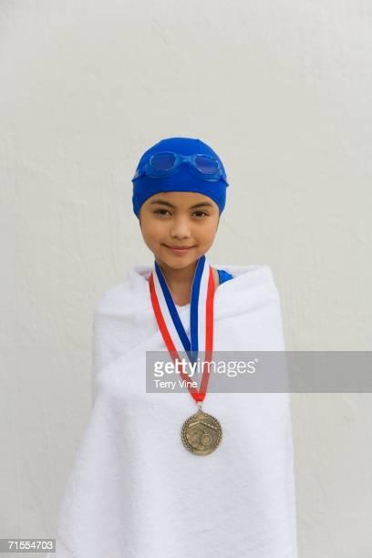 Hispanic girl wrapped in towel with swimming metal