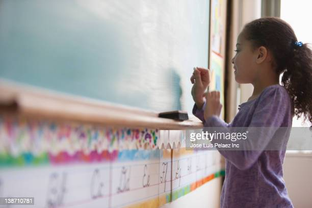 Hispanic girl writing on classroom blackboard