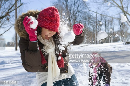 Hispanic girls having snowball fight