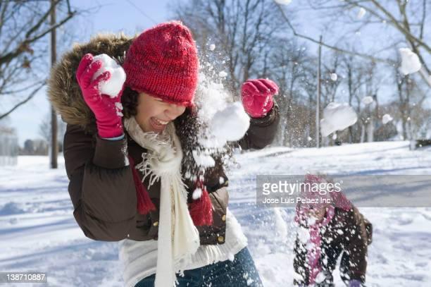 Hispanic girls having snowball fight