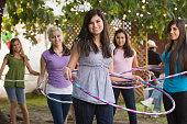 Hispanic girls playing with hula hoops
