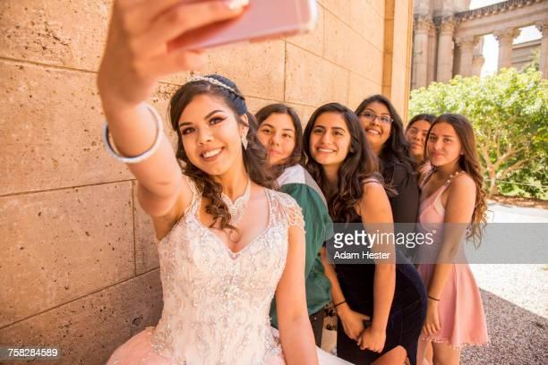 Hispanic girls posing for cell phone selfie
