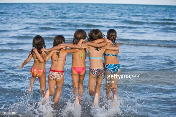 Hispanic girls running through ocean surf