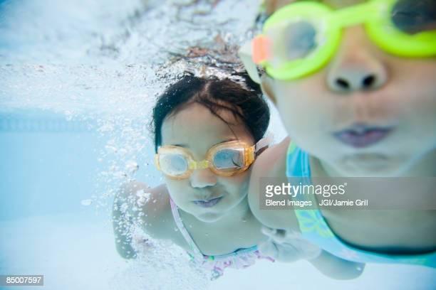 Hispanic girls swimming underwater in pool