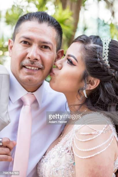 Hispanic girls wearing gown kissing father on cheek