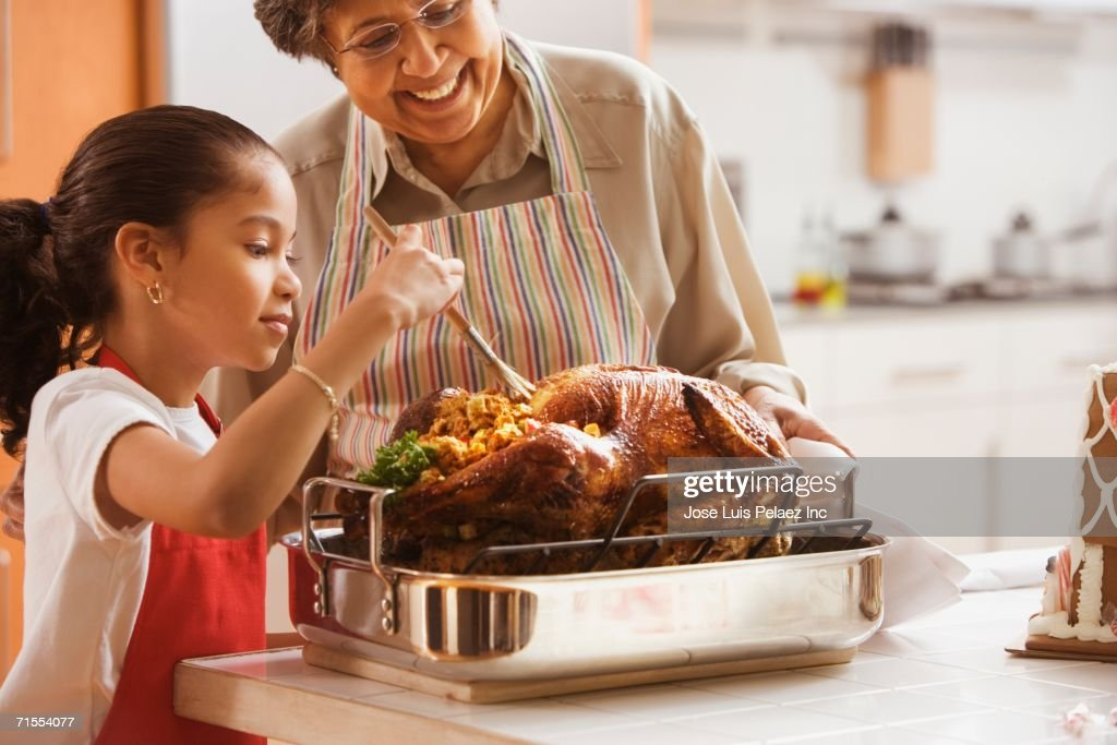 Hispanic granddaughter helping grandmother baste turkey