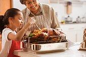 Hispanic granddaughter helping grandmother baste turkey