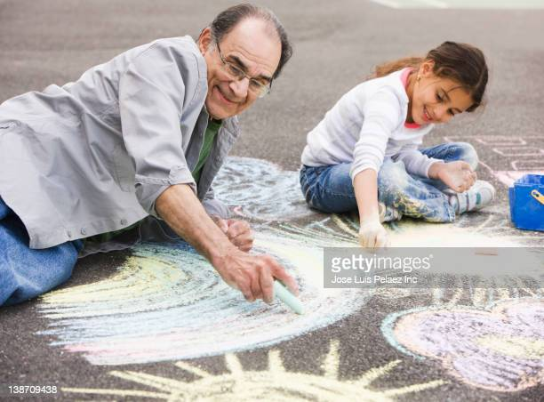 Hispanic grandfather and granddaughter drawing on ground with chalk