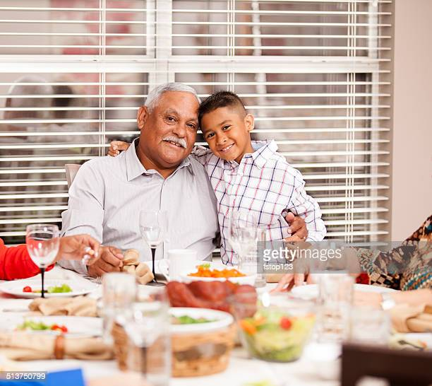 Hispanic grandfather and grandson enjoy family dinner together. Home.