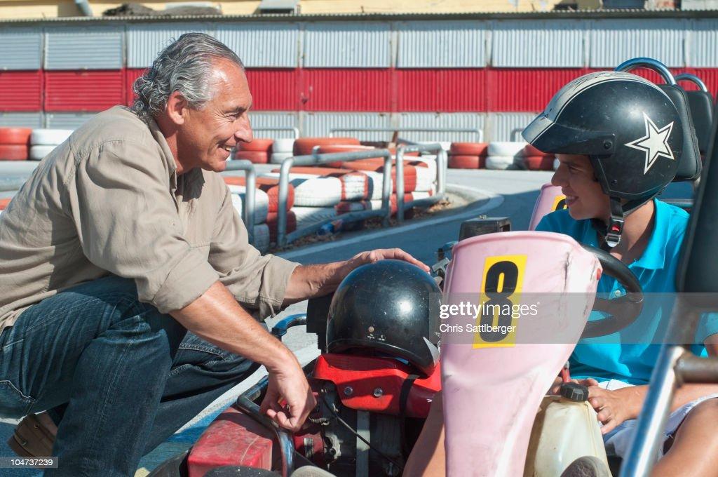 Hispanic grandfather and grandson on go-cart track : Stock Photo