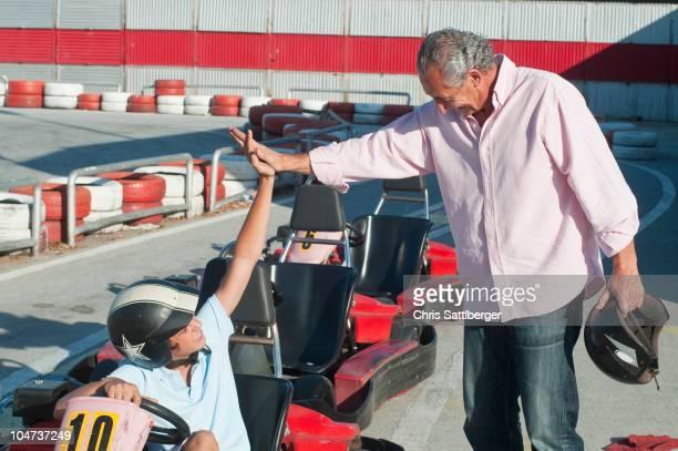 Hispanic grandfather and grandson on go-cart track