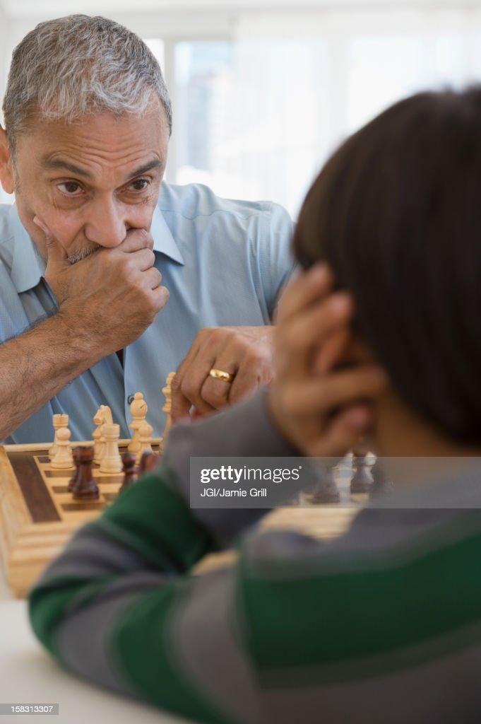 Hispanic grandfather and grandson playing chess : Stock Photo