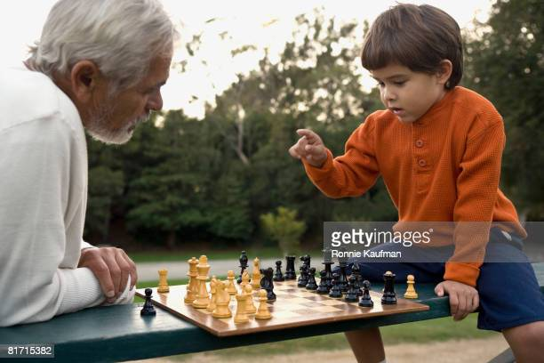 Hispanic grandfather and grandson playing chess