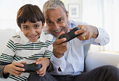 Hispanic grandfather and grandson playing video game