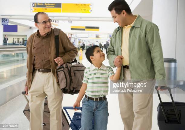 Hispanic grandfather, father and son at airport