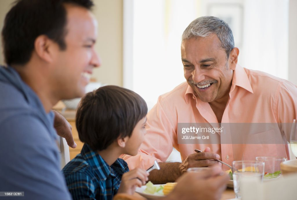 Hispanic grandfather, father and son eating dinner