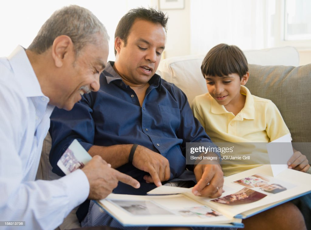 Hispanic grandfather, father and son looking at photo album : Stock Photo