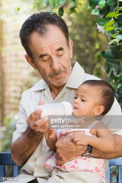 Hispanic grandfather feeding bottle to granddaughter