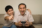 Hispanic grandfather playing video game while grandson looks on