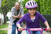 Hispanic grandfather teaching granddaughter to ride bicycle