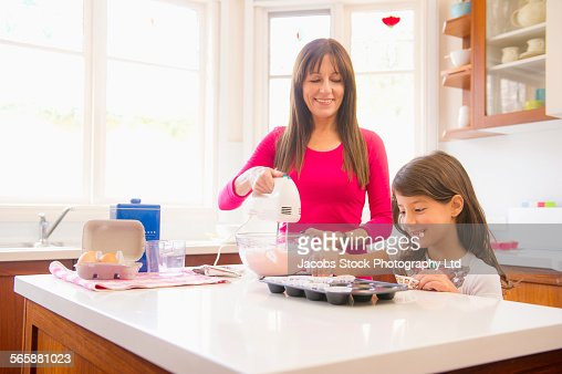 Hispanic grandmother and granddaughter baking in kitchen