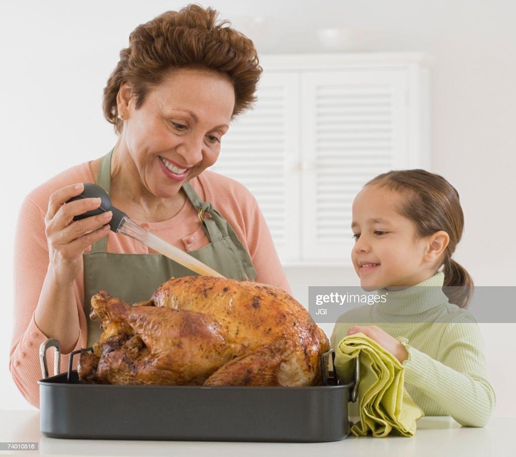 Hispanic grandmother and granddaughter basting roast turkey