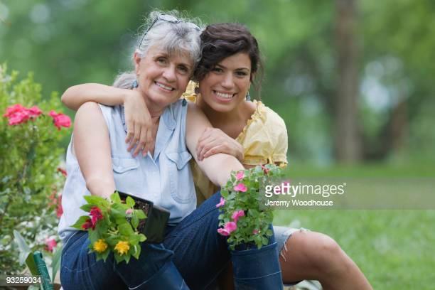Hispanic grandmother and granddaughter gardening