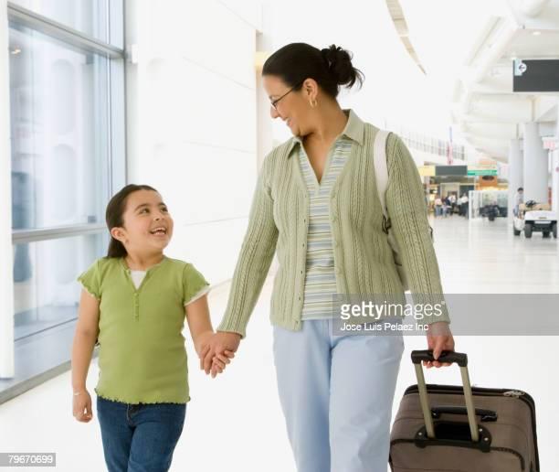 Hispanic grandmother and granddaughter in airport