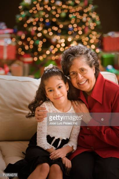 Hispanic grandmother and granddaughter in front of Christmas tree