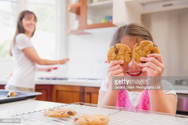 Hispanic grandmother and granddaughter playing with cookies in kitchen