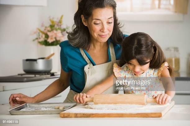Hispanic grandmother and granddaughter rolling dough