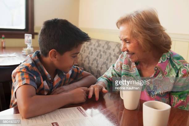 Hispanic grandmother and grandson sitting at restaurant table
