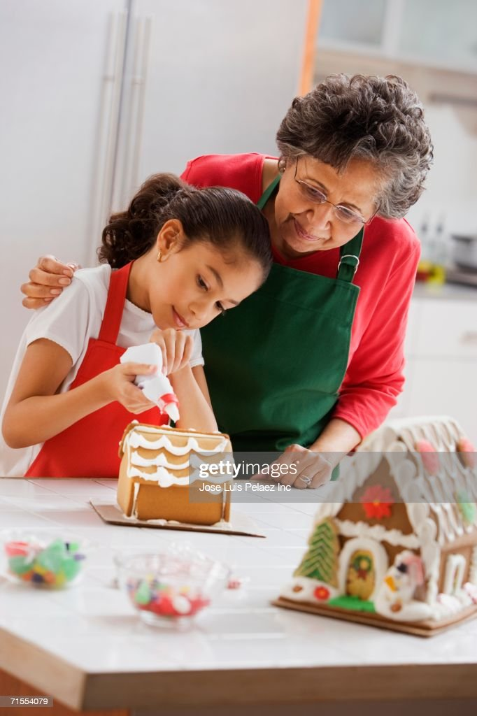 Hispanic grandmother helping granddaughter decorate gingerbread house : Stock Photo