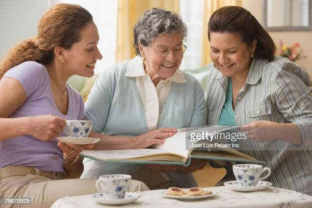 Hispanic grandmother, mother and daughter looking at photographs