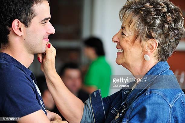 Hispanic grandmother pinching grandsons face