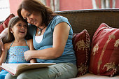 Hispanic grandmother reading to granddaughter