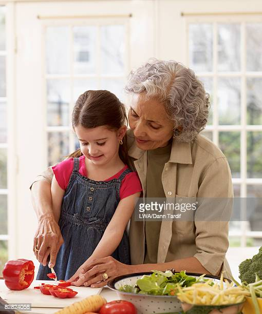 Hispanic grandmother teaching granddaughter how to cook