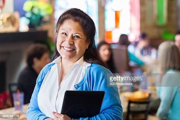 """Hispanic Großmutter mit digitalen tablet in Familienbesitz restaurant """"Tex-Mex"""""""