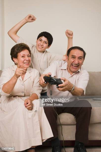Hispanic grandparents and grandson playing video games