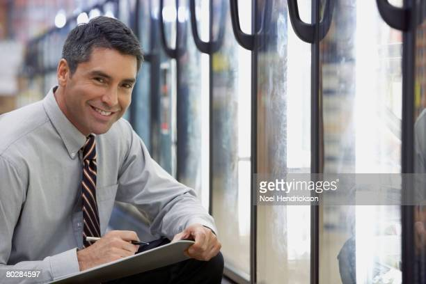Hispanic grocery store manager holding clipboard